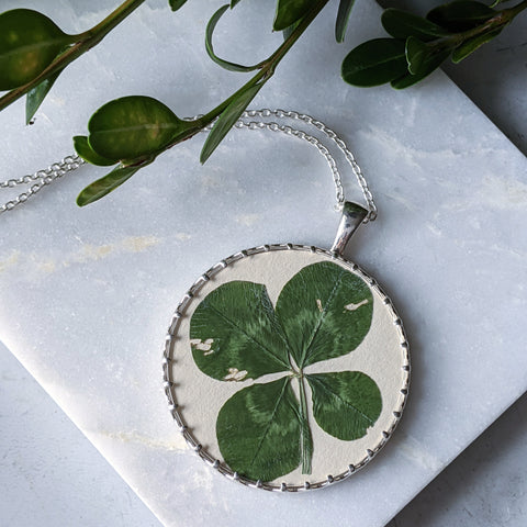 Pressed four leaf clover in a sterling silver and glass pendant. The pendant sits atop a marble slab, with green leaves along the top of the image.