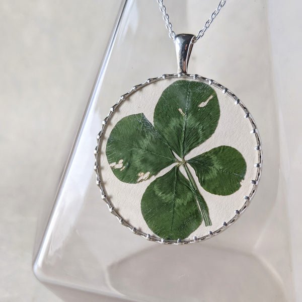 Pressed four leaf clover in a sterling silver and glass pendant. The pendant hangs in front of a clear glass vase.