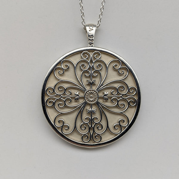 Circle pendant in sterling silver with swirled filigree in a four leaf clover design.