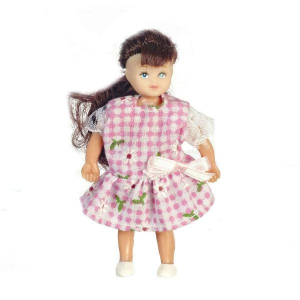 A brunette dollhouse doll wearing a pink and white gingham dress.