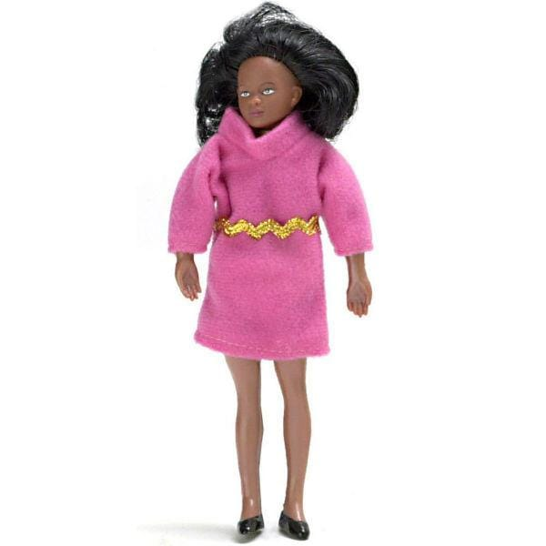 A female African-American dollhouse doll wearing a stylish pink dress and black pumps.