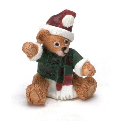 A small Christmas bear that is sitting and wearing festive clothes.