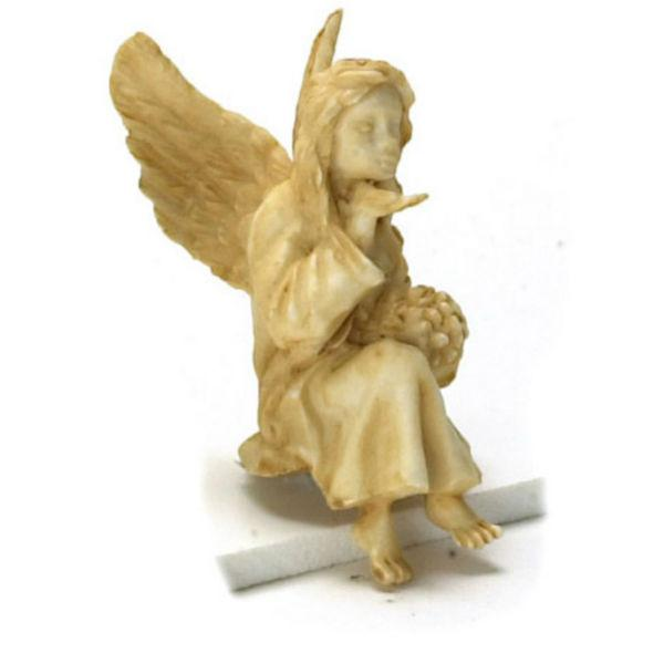 A dollhouse miniature statue of a sitting angel.