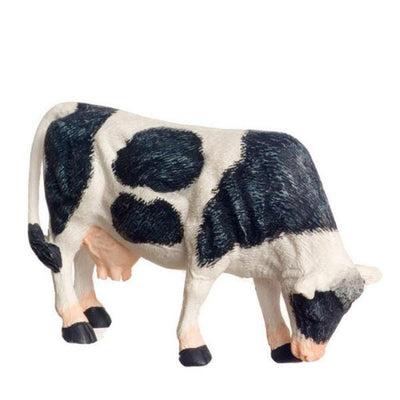 A 1/24 scale miniature cow that is eating.