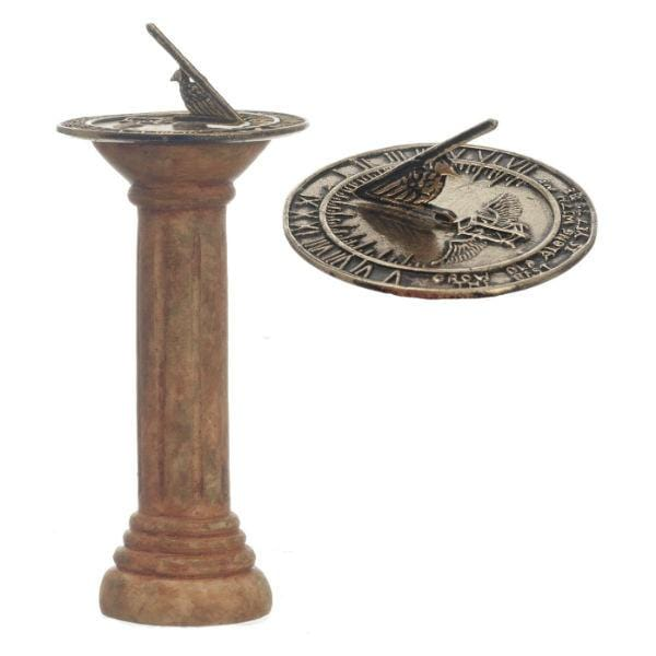 A dollhouse miniature brown pedestal with a sundial on it.