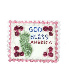 A dollhouse miniature cake with the Statue of Liberty on it and God Bless America written on it.
