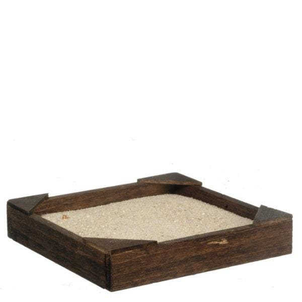 A dollhouse miniature sand box with sand in it.