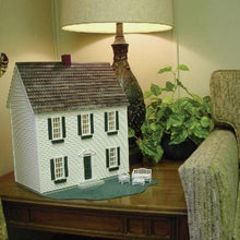 A half scale wood dollhouse kit in a colonial style on an end table.