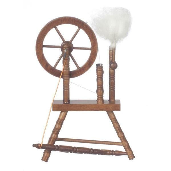 A dollhouse miniature spinning wheel with thread.