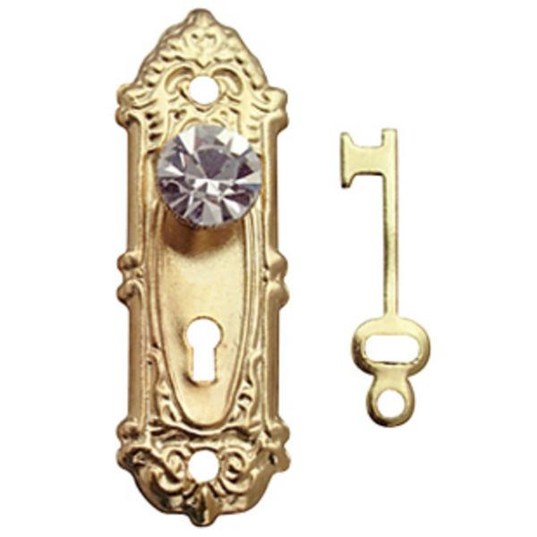 A dollhouse miniature brass and crystal door set with key.