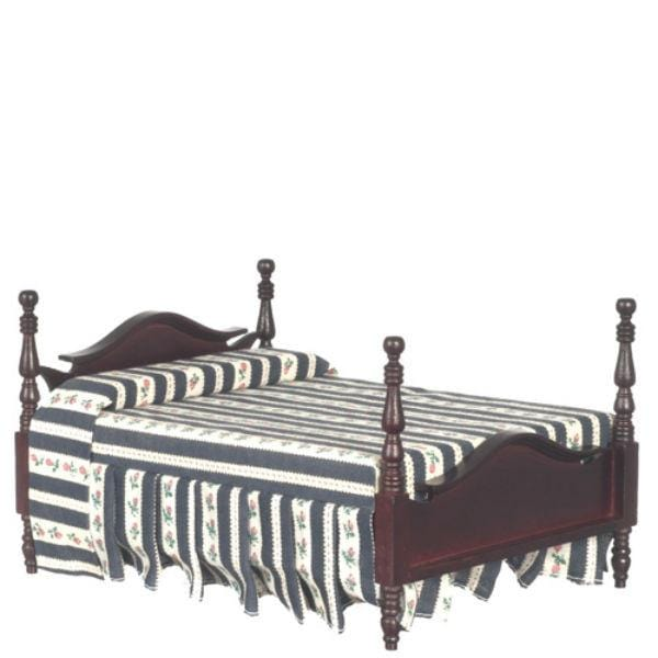A dollhouse furniture bed with striped fabric.