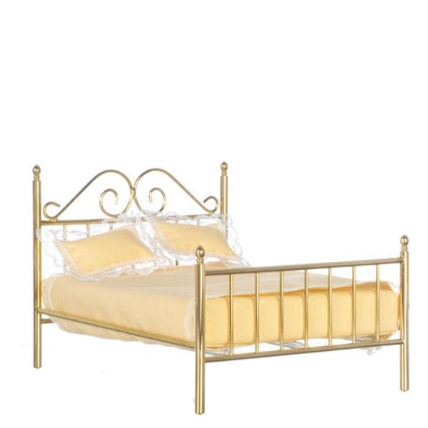 A dollhouse furniture brass bed with yellow mattress and pillows.