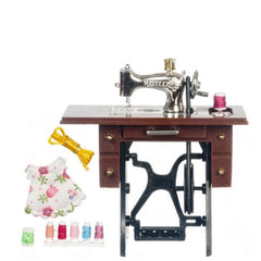A dollhouse miniature sewing machine, table, and sewing accessories.