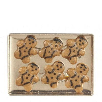 A dollhouse miniature gingerbread men on a cookie sheet.