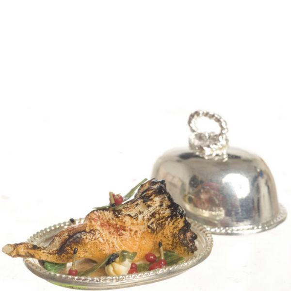 A dollhouse miniature leg of lamb on a covered silver tray.