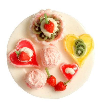 A dollhouse miniature tray of fruit tarts and cupcakes.