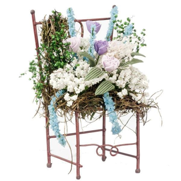 A dollhouse miniature iron chair adorned with lots of flowers.