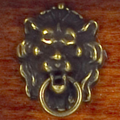 A dollhouse miniature lion's head door knocker.