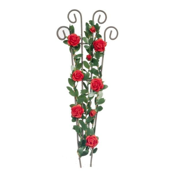 A dollhouse miniature trellis with red flowers on it.