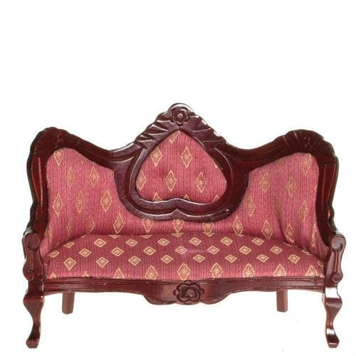 A Victorian dollhouse furniture sofa with pink fabric and a dark wood frame.
