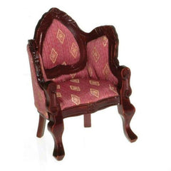 A Victorian dollhouse furniture chair with pink fabric and mahogany-stained wood.