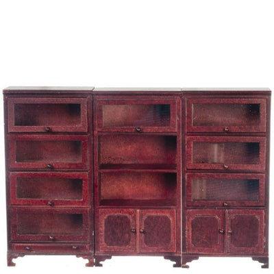 A mahogany dollhouse miniature set of three bookcases with glass doors.