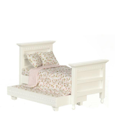 A dollhouse furniture white trundle bed with a pink coverlet and pillows.
