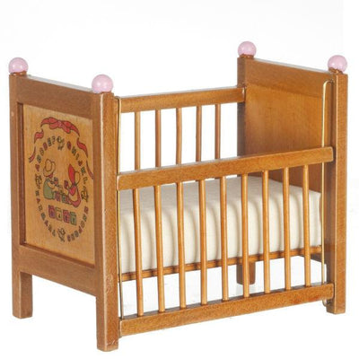 A dollhouse furniture crib with a painted design on the headboard.