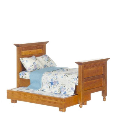 A dollhouse furniture walnut trundle bed with a blue floral cover.