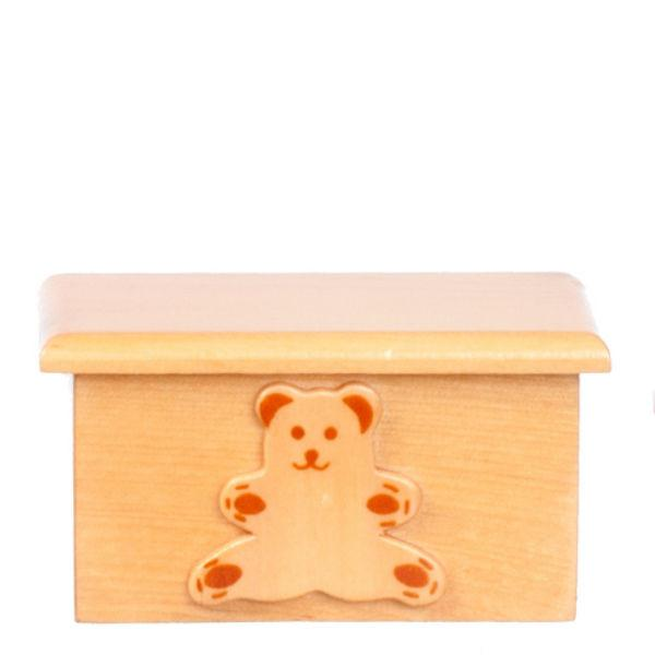 A dollhouse miniature kids' toy box with a teddy bear on it.
