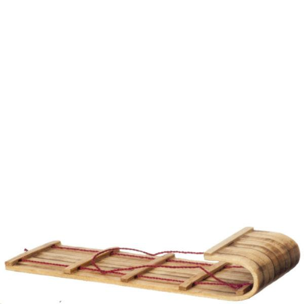 A dollhouse miniature toboggan sled.