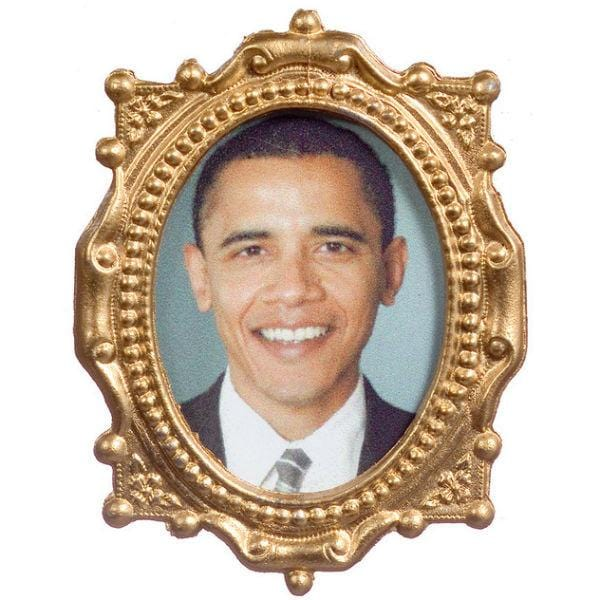 A dollhouse miniature portrait of Barach Obama in a gold frame.