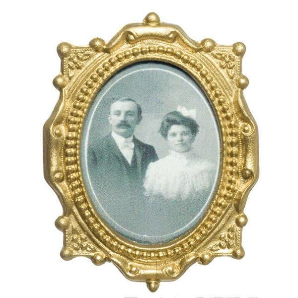 A dollhouse miniature painting of an old-fashioned couple in a gold frame.