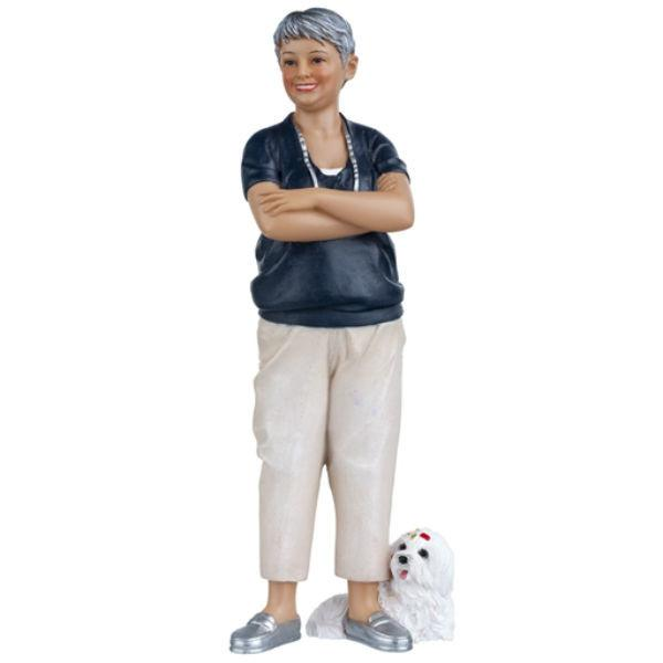 A polyresin dollhouse doll who is an older woman with a little dog.