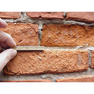 Take out a sample piece from the Ecologic Lime Mortar Kit for a side-by-side comparison to the existing old mortar.