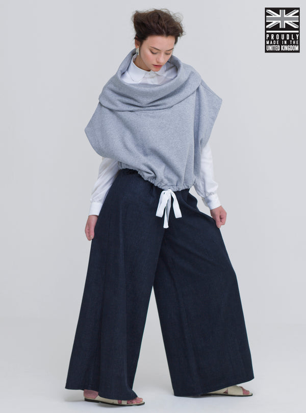 Who said being eco conscious has to be boring. Woman wearing organic cotton winter poncho. Ethically made in the UK. Minimal style, part of our sustainable fashion collection.