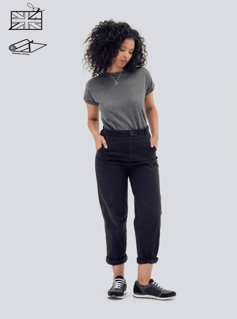 Model wearing zola amour ethical fashion organic cotton black trousers – with button on and off paper bag frill.