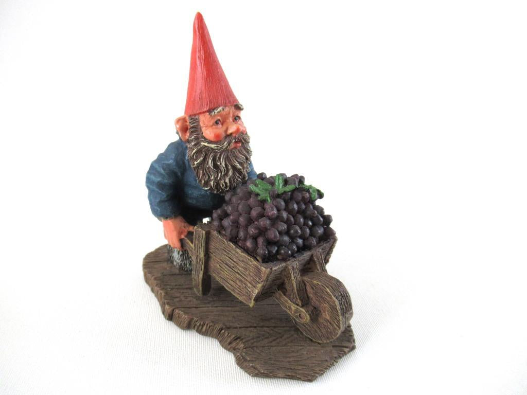 Gnome figurine transporting grapes with a wheelbarrow.  'Christian' Classic gnomes series after a design by Rien Poortvliet.