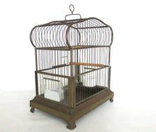 UpperDutch:,Antique German Bird Cage with porcelain feeders and glass panels on both sides.
