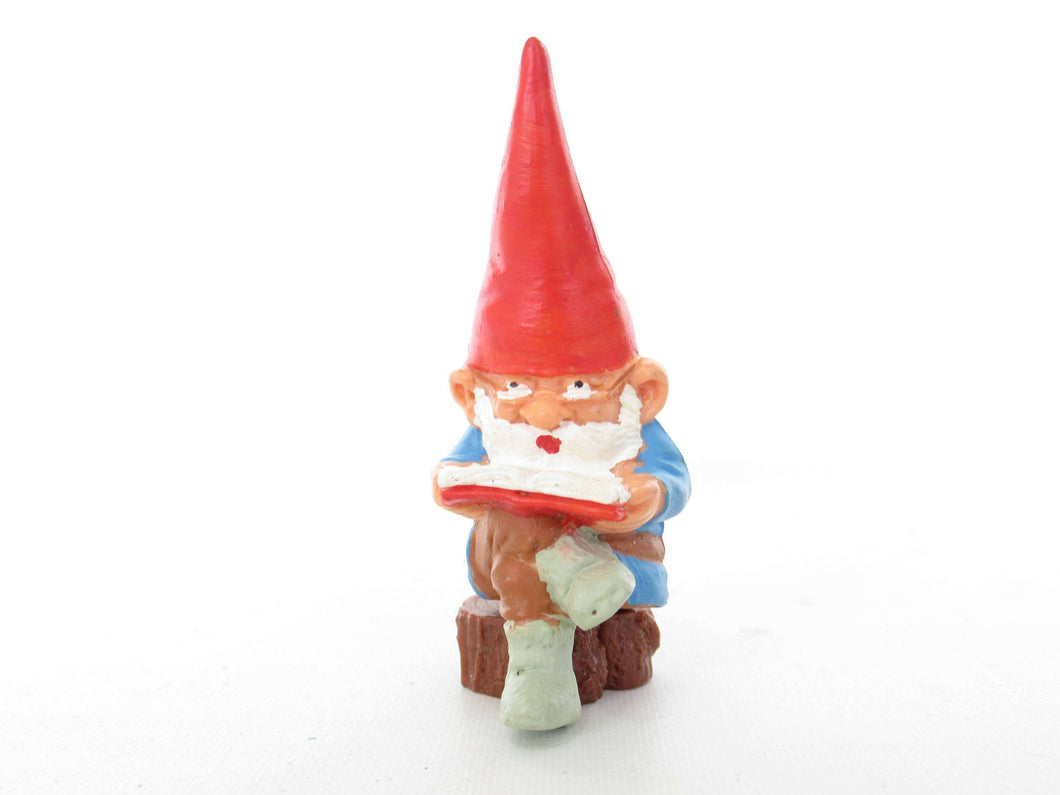 UpperDutch:,1 (ONE) Gnome, miniature Gnome after a design by Rien Poortvliet, Brb. David the Gnome, reading gnome sitting on a tree trunk.