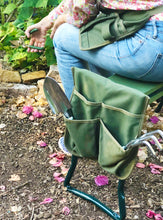 woman wearing green apron sits on garden seat/kneeler in garden and holds pruner
