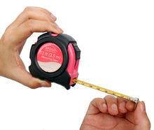two hands opening a pink tape measure