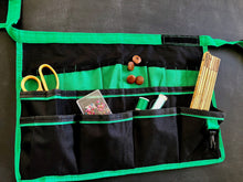 green and black bucket organizer shown flat with hobbies accessories for sewing