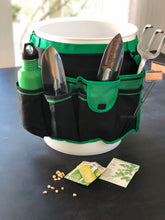 green and black bucket organizer with seeds, garden tool, green water bottle