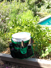 green and black bucket organizer around a white bucket, garden and pool in background