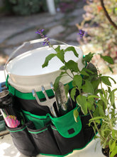 green bucket organizer filled with tools and water flask surrounded by plants