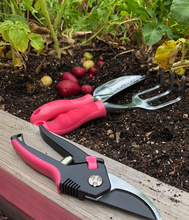 Pink Pruning Shears,  trowel and rake next to garden harvest potatoes