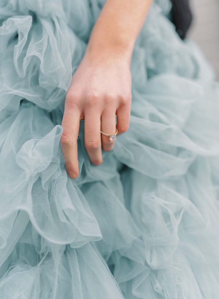 Woman wearing engagement ring and blue ruffled dress