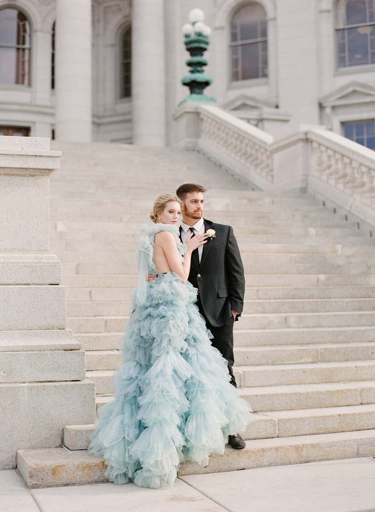 Woman in blue gown and man stand on the wisconsin capitol stairs