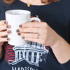 Twisted band engagement ring holding coffee cup